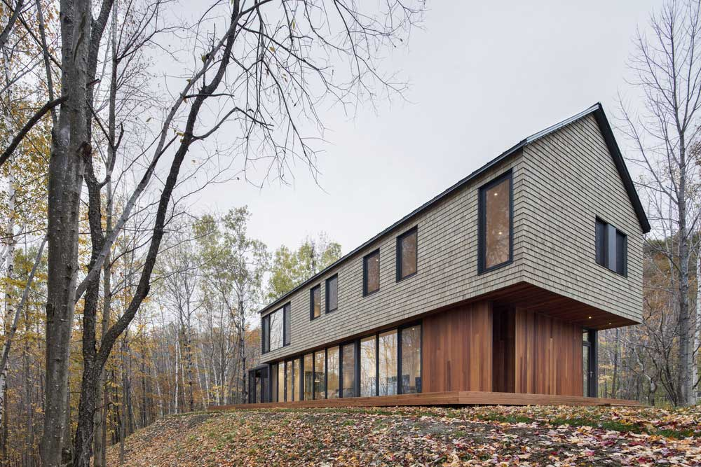 Modern forest home with cedar shingles and glazed openings for Modern roof shingles