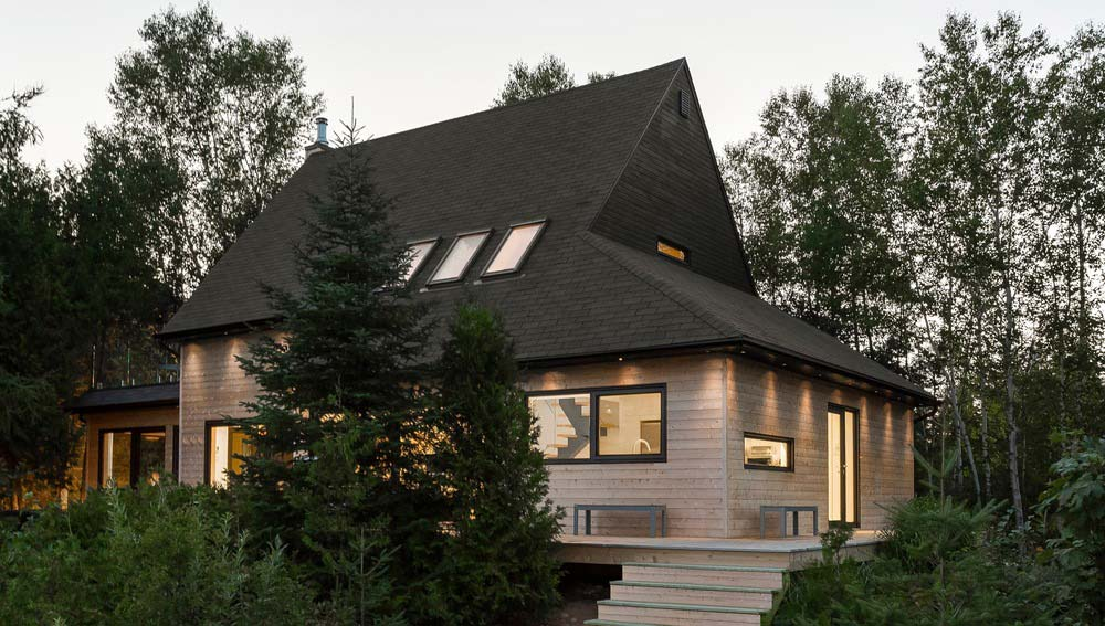 Modern lake cottage with nordic inspired design in saint for Lakefront cottage plans canada